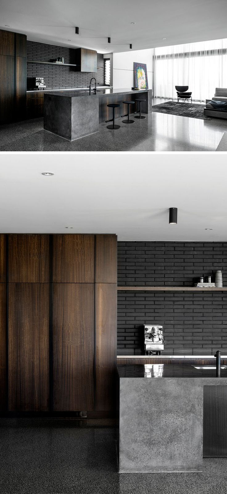 Dark brick has been paired with dark wood cabinets and a concrete island in this modern kitchen. #ModernKitchen #DarkBrick #Concrete