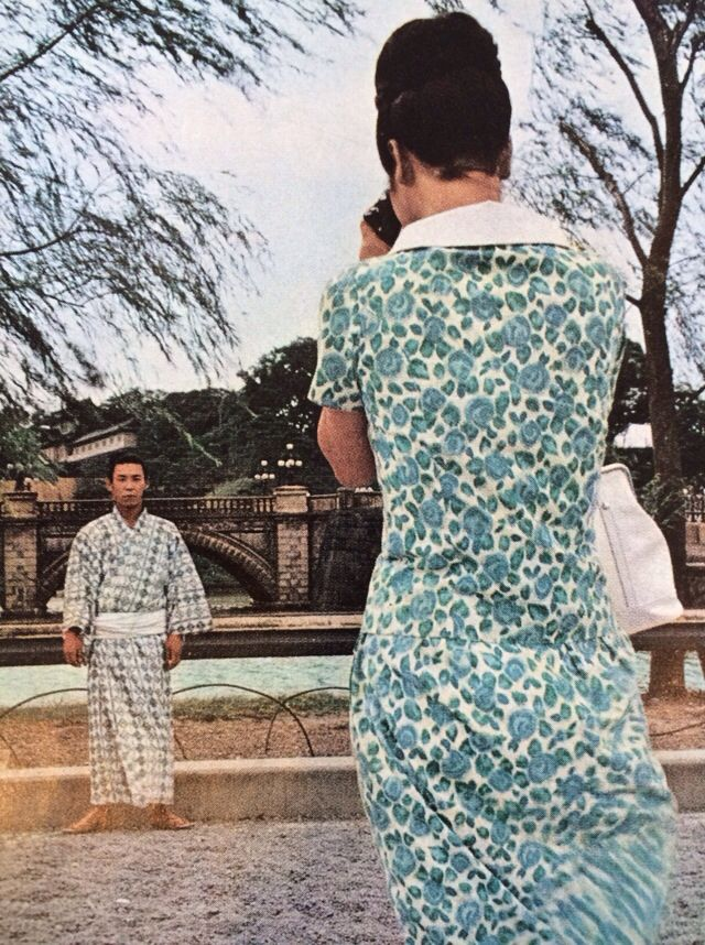 Tokyo 1964. Woman in western dress taking photo of man in kimono. Color.