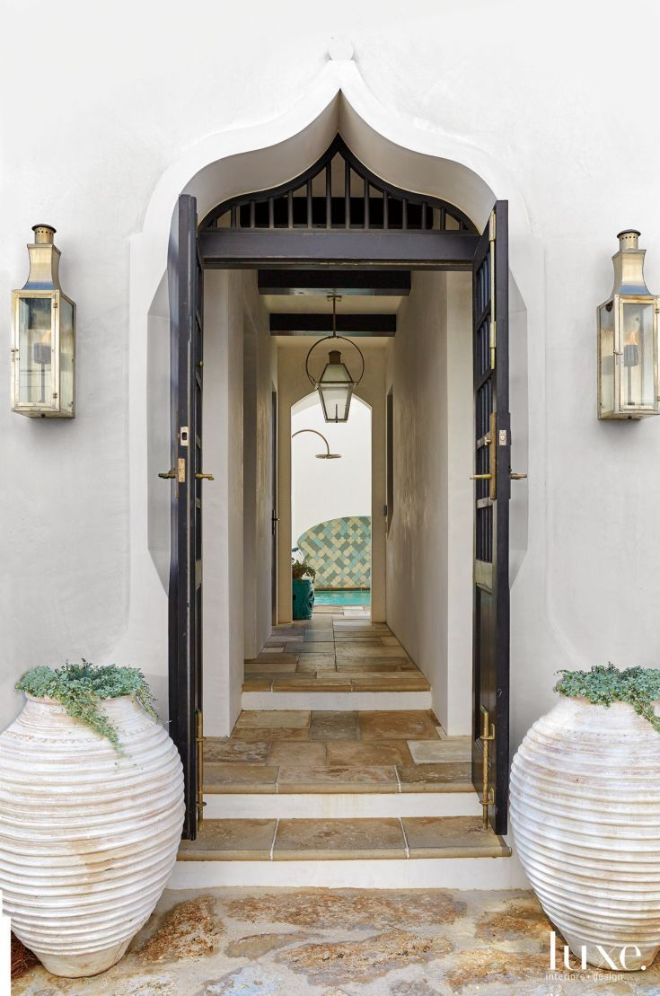 A pair of ribbed stone pots and lanterns by Bevolo Gas and Electric Lights frame the passageway that leads into the house, up to the kitchen, and to the pool courtyard ahead. Paneled doors with a strong grid design, from E. F. San Juan, fit into an arched stucco frame; they reference Moorish architecture.