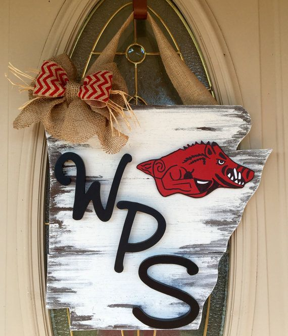 Handcrafted from pinewood, these signs come stained or distressed, in script letter monogramming You choose the bow color. All letters will be black as shown.  This is special Woooo Pig Sooie Arkansas edition. The dimensions of Arkansas are approximately 16 x 16.5 inches.  Will hang nicely from a wreath hanger on your door.  Because each of our pieces is hand cut from wood that can have a rough texture, knots, small cracks or other imperfections that add to its rustic nature, painted with…
