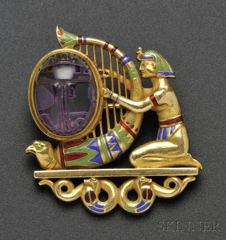 Fine Jewelry - Sale 2586B - Lot 495     Egyptian Revival Amethyst and Enamel Brooch, T.B. Starr, the kneeling figure with headdress and armbands, playing a harp set with an amethyst scarab, with falcon head and lotus blossom motifs, the falcon with demantoid garnet eye, on snake supports, polychrome enamel accents, reverse engraved, 1 1/4 x 1 1/8 in., signed.  Overall very good, minor wear with age.    Sold for $10,073.00