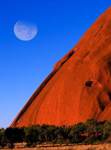 Uluru , también conocida como Ayers Rock and officially gazetted as Uluru / Ayers Rock, is una gran sandstone rock formation en la parte sur of the Northern Territory, central Australia. It lies 335 km (208 millas) south west of the grande más cercana town, Alice Springs, 450 km (280 millas) por carretera.