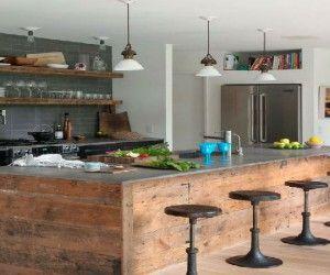 Dans une cuisine esprit industriel se mélange matériaux design en bois, inox comme le plan de travail, des murs brut style loft en briques ou pierres apparantes