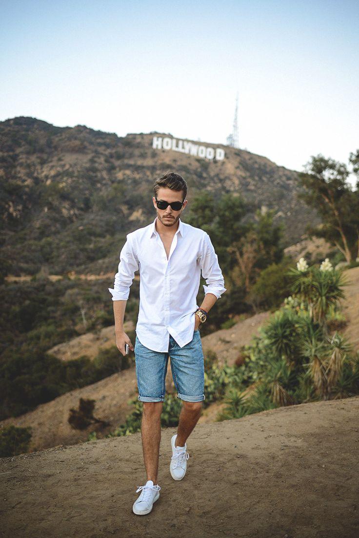 Él está llevando azul pantalones cortos. Él lleva blanco la camisa y negro lentes de sol. Un luna pantalones cortos veinte. Un luna camisa diez dólares. Un luna lentes de sol quince dólares.
