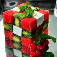 """10 kiwi 1 med. watermelon 1 lb. feta cheese in large pieces (not crumbled) mint leaves berries (your choice) 1/2 c. light olive oil 1/4 c. balsamic vinegar ground black pepper to taste Cut fruit & cheese into 1"""" cubes. Place 5 watermelon in checkerboard pattern, 2 cubes kiwi & 2 cheese in opposite directions. 2nd layer w/kiwi in the corners & cheese/melon in open spaces. 3rd layer same as 1st. Whisk oil & vinegar w/pepper, pour around cube. Garnish w/mint & spread berries around plate."""