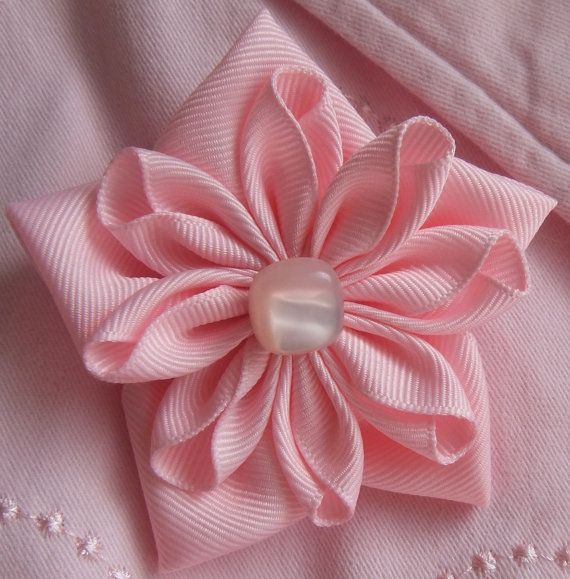This pretty in pink flower pin is handmade from grosgrain ribbon. Each petal was cut, folded, heat-sealed to prevent fraying, and then the two layers were glued together. The petals were made using two different Kanzashi techniques. A pink square pearl like button was glued in the center. On the back is a silver pin which was hand sewn to felt and glued to the flower. This flower pin/brooch is approximately 3 1/8 wide. You can wear this flower on a blouse, blazer, coat, sweater, s...