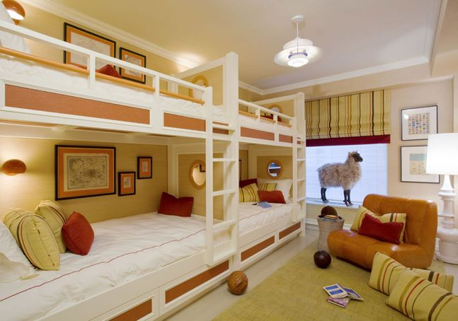fun yellow & orange boy's room with four bunk beds, white hotel bedding with orange stitching, yellow & red pillows, citrine rug, orange leather tufted bench and yellow green black striped roman shade.