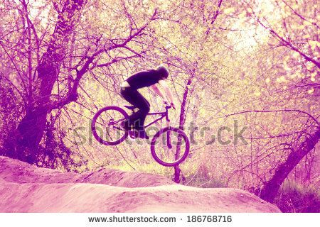a biker riding a bicycle over a jump done with a retro vintage instagram like filter  - stock photo