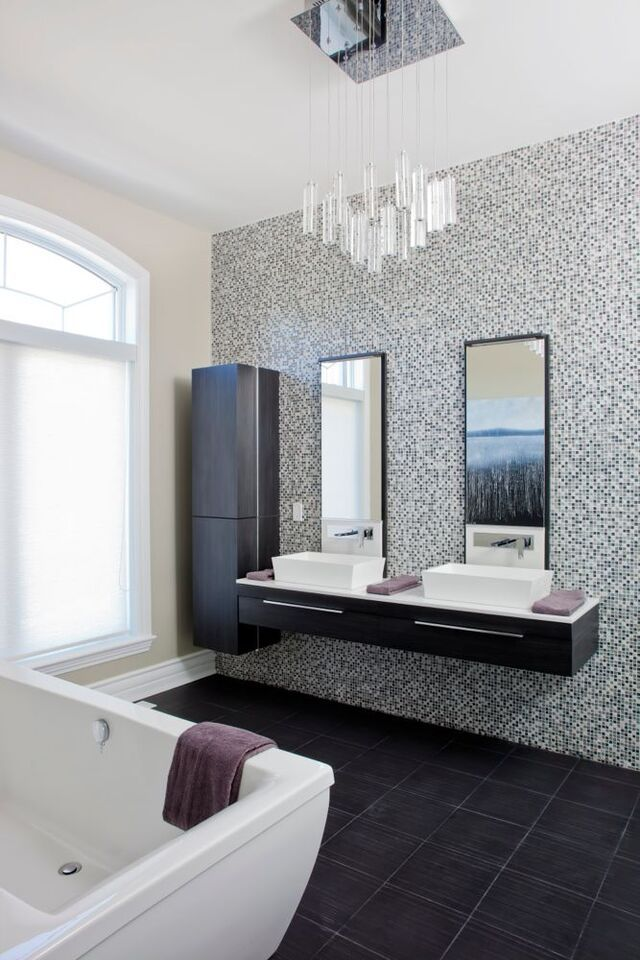 The delicate chandelier hanging in this bathroom sets a tone for the rest of the space, with a speckled tile wall behind the sinks, and a deep black tile floor, this bathroom is modern and sleek.