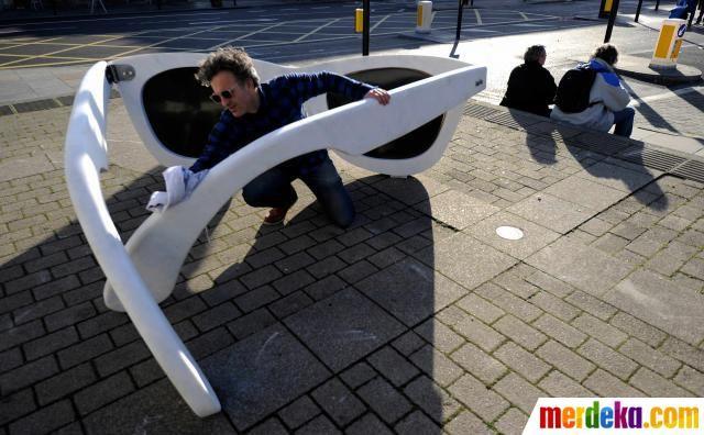 Artis Joel Gray berpose untuk difoto dengan patung kacamata raksasa di London, Inggris.