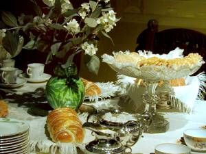 Man har släppt in solen, ljuset och naturen i hemmet. Vilda blommor pryder kaffebordet. Sju sorters kakor, vetebröd och sockerkaka är framsatta. Tack vare järnspisen med bakugn, jästpulvret, pressjästen och det inhemskt odlade vetet, kan husmor baka en helt annan sorts bröd än tidigare. Kaffekalas blir ett omtyckt nöje. Kanske någon saknar gräddtårtan? Inte förrän på 1920-talet kommer den på kaffebordet, den tillhörde länge en av festmiddagens många rätter. Foto: Mats Landin, Nordiska…