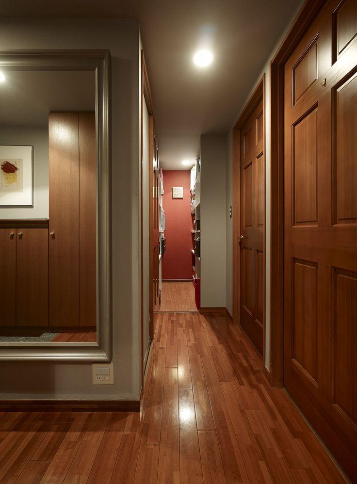 【#ミサワホームイングデザインリフォーム 】マンションのリノベーション。玄関は重厚感のある仕様でコーディネートしました。大きなミラーの額縁や框ドアの装飾パネルがクラッシックなインテリアのポイント。赤みがかった艶のあるフローリングとドアが高級感を漂わせています。廊下の奥に設けた納戸で住まいの収納量を確保。扉を開けた正面のアクセント壁の赤が印象的です。 #リフォーム #リノベーション #住まい #インテリア #インテリアデザイン #インテリアコーディネート #マンション #マンションリノベーション #マンションリフォーム #マンションインテリア #玄関 #玄関収納 #玄関インテリア #玄関リフォーム #ミラー #納戸 #赤 #框ドア #廊下 #ミサワホームイング #intelimia