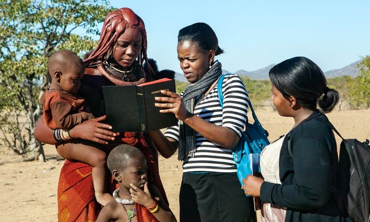 Two of Jehovah's Witnesses preach to a Himba woman in Namibia