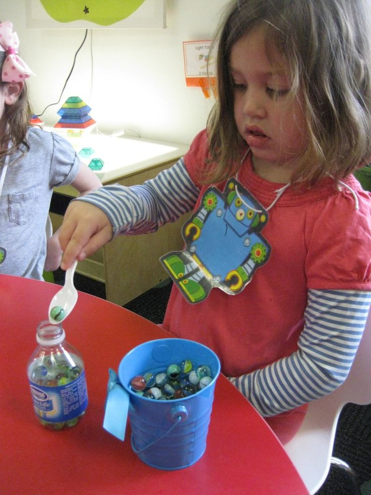 Fine motor skills spoon marbles into water bottle -- can combine this with counting, sorting, counting, etc