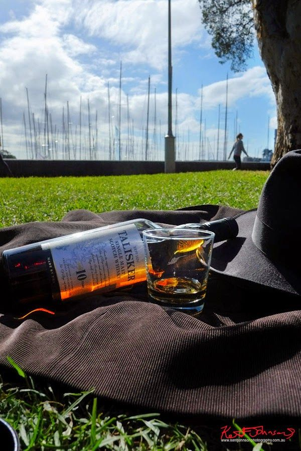 Talisker Whisky, the hat jacket and a single glass of whisky still life photographed in a Sydney Harbour Park, social media marketing and promotion.
