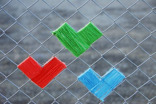 Wrap yarn around links in a chain link fence. Makes me think of tucking in crocheted granny squares.