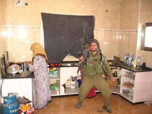 A fully-armed Israeli soldier preens for the camera while a Palestinian mother attempts to ignore the humiliation of having her kitchen invaded, during Operation Cast Lead;when Israel killed over 1,400 Palestinians, including 300 children. (Photo credit: Assaf Kintzer)    Uncivilized and disrespectful bastard, who shouldn't be there in the first place.