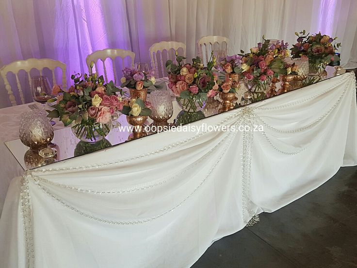 Beautiful main table for the bridal couple draped with loops of crystal detail. Flowers in shades of purple and pink with rose gold bowls and glass decor elements. Elegance!