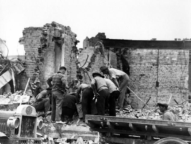 Searching the Rubble, Napier.  The photograph shows unidentified men searching the rubble for the injured and dead, after the devastating 3 February 1931 earthquake and subsequent fire. The exterior walls are all that remain of the building. Cyril Walter Lambourne, photographer. Post 03 Feb 1931