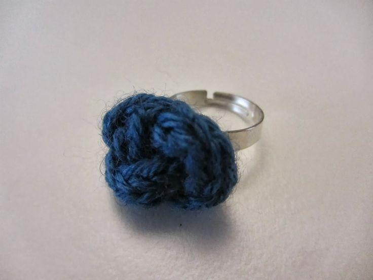 """Anello """"nodo"""" in lana lavorata a crochet, montato su base anallergica regolabile."""
