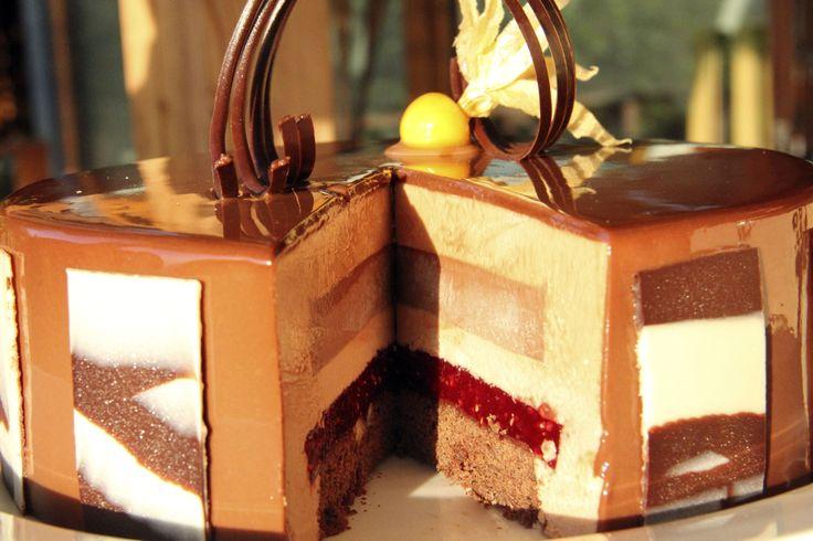 Torta Seducción. Bizcocho Brownie, gelatina de frambuesa – maracuyá, cremoso de avellanas, mousse de cobertura de leche.