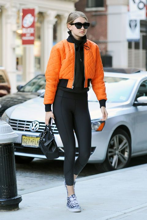 Out in NYC wearing an orange bomber jacket with black leggings and printed sneakers.