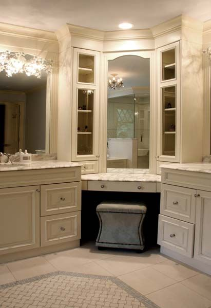 Gorgeous bathroom design with gray vanity ottoman tucked under corner vanity accented with inset mirror and glass-front cabinets flanked by his and her vanities featuring ivory cabinets paired with white marble countertops and sconces mounted on inset mirrors.