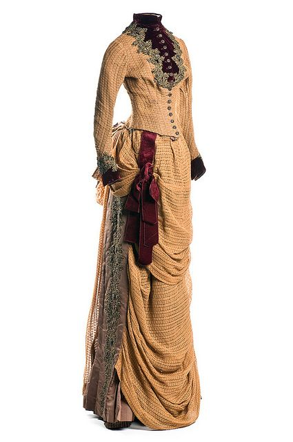 Woman's tan open-weave linen dress, c. 1880. The corseted bodice is trimmed with maroon velvet and metallic beading; the brown faille skirt is draped with matching linen forming a bustle in back and apron drapery in front. From the Seasonal Fashion: Autumn exhibit at The Charleston (South Carolina) Museum.