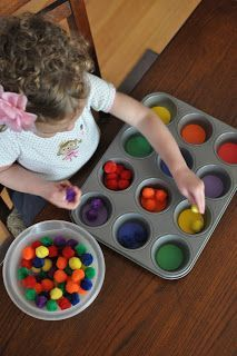 Sorting colored pom poms in a cupcake tin activity- great way to learn dexterity, color matching, and to pass time