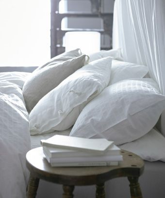 White pillows and blankets on a bed with a bedside table stacked with books next to it.