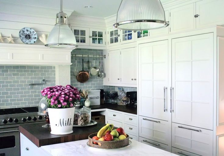 white kitchen brick walls pendant lights flowers stove faucet wall rack wall cabinet marble countertop of White Kitchen Designs to Get Inspirations From