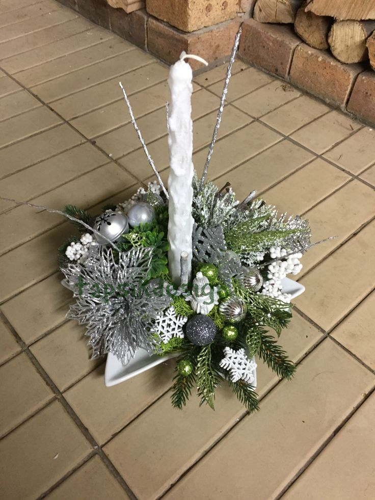 Christmas candle centerpiece with snowman. In the color of white-silver-green. Full of christmas decorations.
