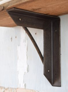 "Hand-hammered metal shelf bracket with blackened iron finish. Connected with hammered rivets for an industrial look. This shelf bracket measures 11 1/4"" x 9"" x 2"" We recommend a shelf bracket every 36"