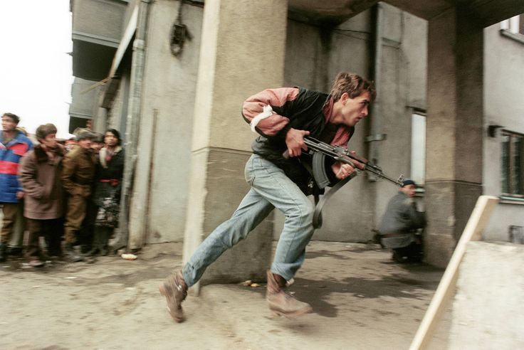 An anti-Communist civilian fighter armed with a Kalashnikov, chases members of the Securitate (the communist secret police) loyal to Nicolae Ceausescu, during the Romanian Revolution, downtown Bucharest, December 24, 1989