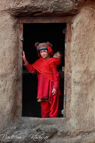 A young girl with her younger family member at the door to her house, Gilgit Baltistan, Pakistan. Gilgit–Baltistan is the northernmost territory of Pakistan. (V)