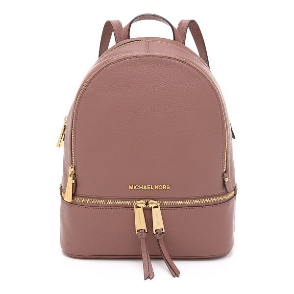 A structured MICHAEL Michael Kors backpack in pebbled leather. Polished logo lettering accents the front. 2 zip front pockets. Wraparound top zip and