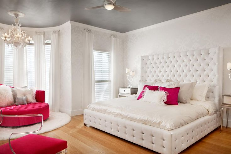 A tufted platform bed with a high headboard creates a luxurious atmosphere in this airy white bedroom. Hot pink accents, a silver ceiling and an elegant chandelier balance playfulness with glamor.