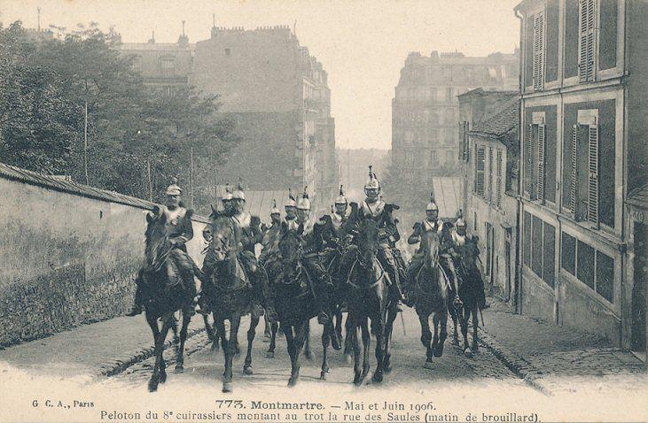 Un peleton du 8e cuirassiers montant au trot la rue des Saules, un matin de brouillard, mai et juin 1906  (Paris 18ème)