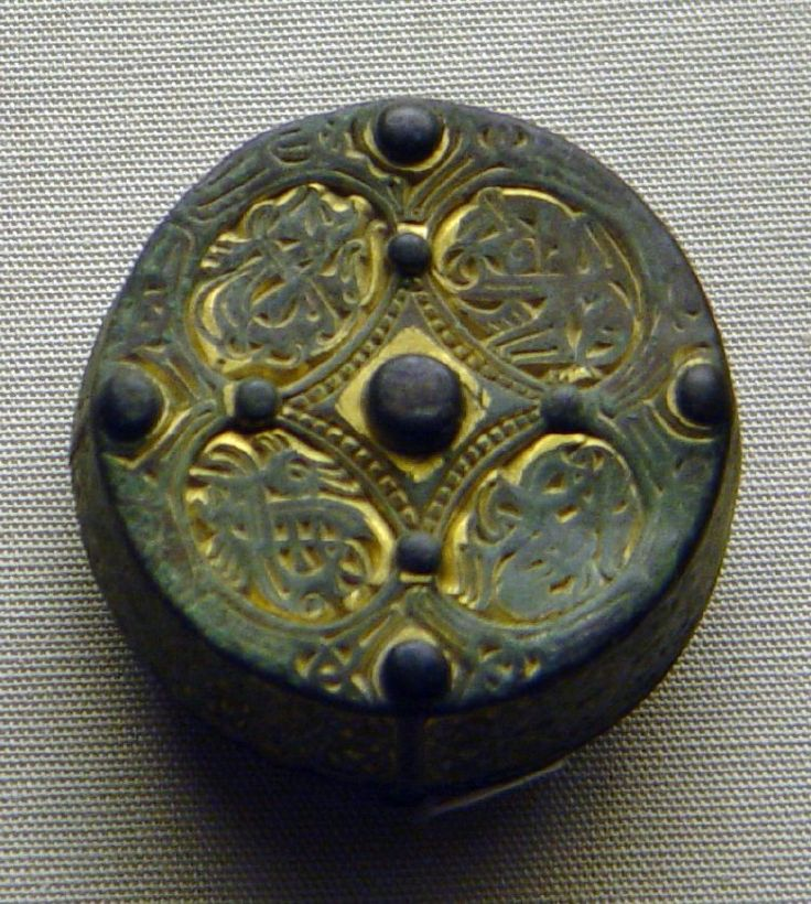 Gilt copper alloy disc-on-bow brooch base-plate from composite applied disc; side panels with Style III animal interlace and Gripping-Beast motifs decoration; 4 kidney-shaped fields of cast degenerate animal decoration on back.