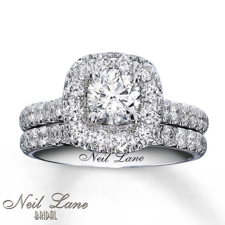 Inspired by vintage Hollywood style, beautifully designed by Neil Lane. Round diamonds brilliantly frame a magnificent round diamond in this ravishing engagement ring for her. Rows of round diamonds sparkle on either side of the 14K white gold band and line the matching wedding band. Each Neil Lane Bridal® ring is hand-crafted and undergoes a four-step polishing process which gives the ring its beautiful shine and luster. The bridal set has a total diamond weight of 1 7/8 carats and feat...