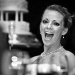 Bride laughing during the speeches, tiered wedding cake in the background
