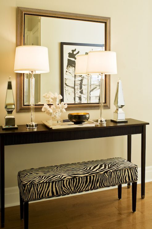 Chic Foyer Features A Long Zebra Bench Tucked Under A Black Console Table  Topped With Tall Crystal Table Lamps, Mirrored Obelisks Under A Square  Beaded ...