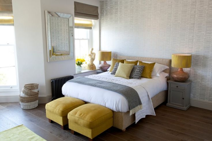 beach themed bedroom design with textured and silver wallpaper grey and mustard yellow bed accessories a couple of yellow ottoman chairs dark hardwood floors grey bedside tables silver framed mirror of Brilliant Ideas of Wall Combination for Light Yellow