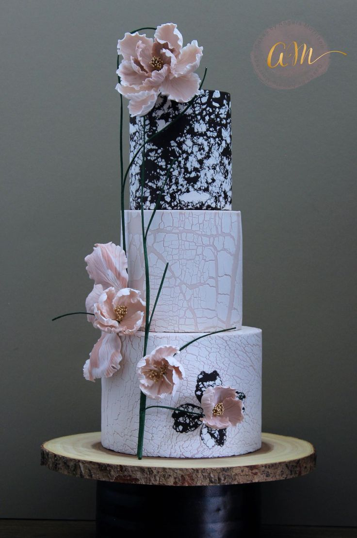 Modern black, white, and blush cake with three tiers of differing crackled marble designs. The soft pink flowers with sharp green stems accent this wedding cake perfectly!  |  Cake Design: Cakes by Angela Morrison