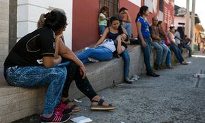 Elena Cruz and her mother, sit outside Comar in the Tapachula, seeking refugee status.