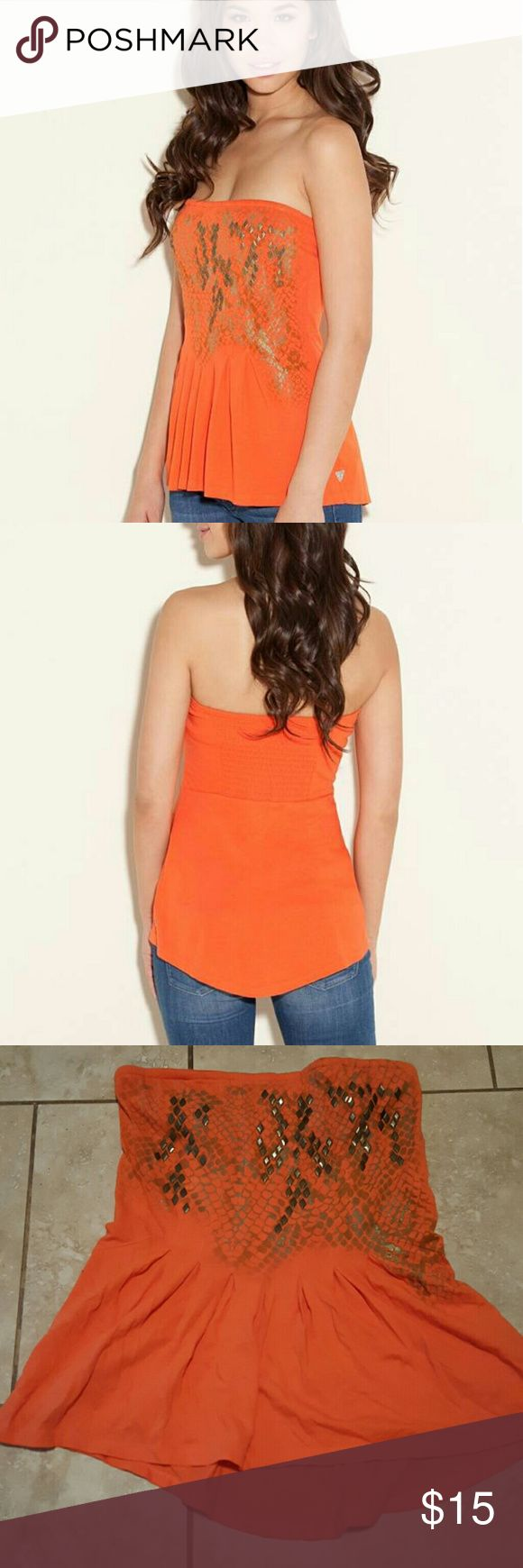 Guess Frida Orange Tube Peplum Top Size S Spend your summer days in this bright, breezy tube top. The metallic print and brass-tone studs add extra detail to the of-the-moment bright colors.    Tube top with straight neckline Scale print on front with studs. Pleats at front waist. Smocked panel at upper back.  100% Cotton Hand wash PRE-OWNED HAS MULTIPLE SPOTS WERE THE THREAD IS LOOSE OR COMING OFF Guess Tops