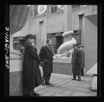 """""""United Nations"""" exhibition of photographs presented by the United States Office of War Information (OWI) on Rockefeller Plaza. Listening to broadcasts of President Roosevelt, Churchill, Stalin, and Chiang Kai-Chek, heard every half-hour from a loudspeaker at one end of the frame containing the Atlantic charter. This frame is surrounded by four statues of the four freedoms. Library of Congress, Call Number LC-USW3- 018411-E [P&P]"""