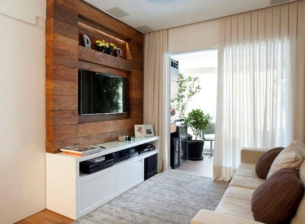 Na sala de estar, o painel de madeira executado pela Marcenaria Piñeiro contrasta com as cores claras dos móveis, como o sofá na Inkasa. Projeto de Beatriz Quinelato publicado em Casa e Jardim (Foto: Adriana Barbosa/Divulgação)