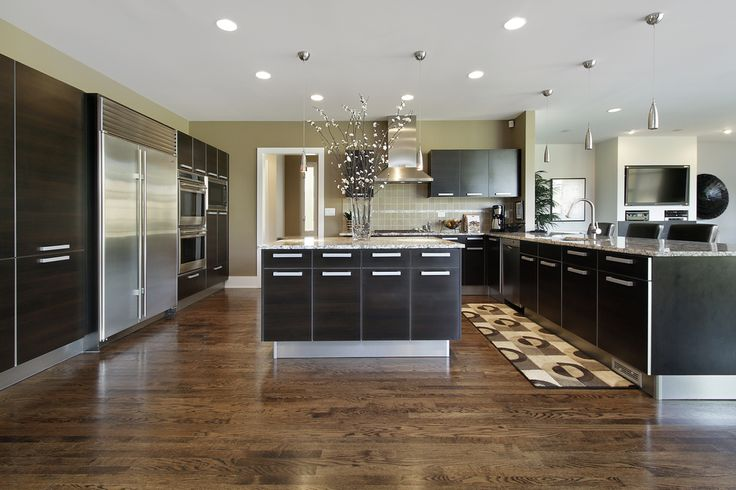 Large kitchen with dark cabinets with stainless steel fixtures