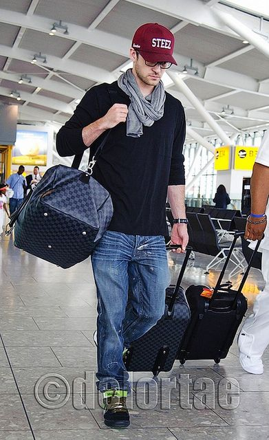 """Justin Timberlake carrying Louis Vuitton Luggage    Justin Timberlake was seen walking through London's Heathrow Airport wearing a burgundy """"Steez"""" hat created by Primitive in collaboration with skater Chaz Ortiz. Wearing a pair of Nikes, carrying a Louis Vuitton Damier Graphite Roadster bag while pulling LV Damier Graphite Pegase Luggage.    UK's exclusive luxury authentic handbag SPA   Visit us on Facebook: www.facebook.com/DelortaeAgency"""